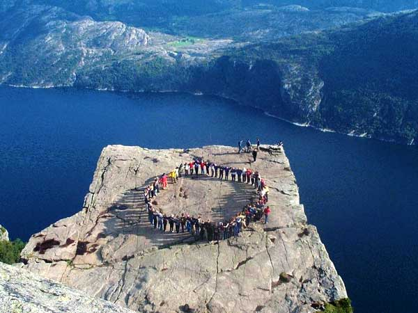 Dança em círculo em um precipício Preikestolen.  Foto