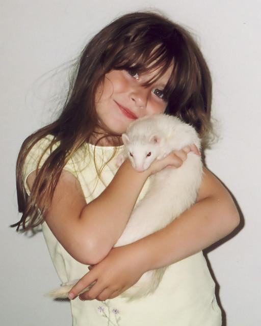 Девочка обнимает белого хорька. Фото
