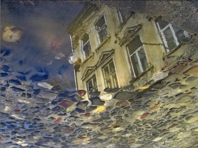 Отражение дома в луже. Фото