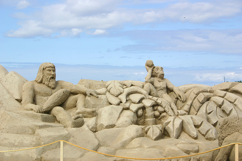 Первобытный человек и обезьяна против льва. скульптура из песка, Лаппеенранта, Финляндия. фото