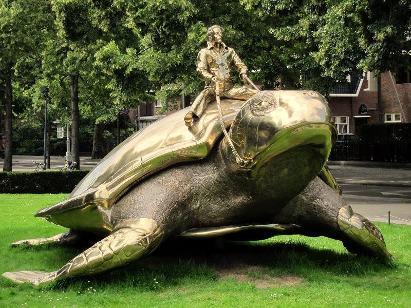 Памятник- человек сидящий на черепахе в Амстердаме. Фото